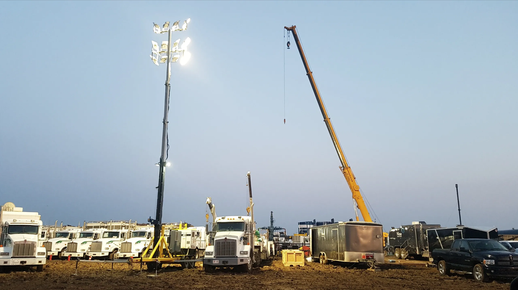 Light tower, crane and several hauling trucks on a worksite