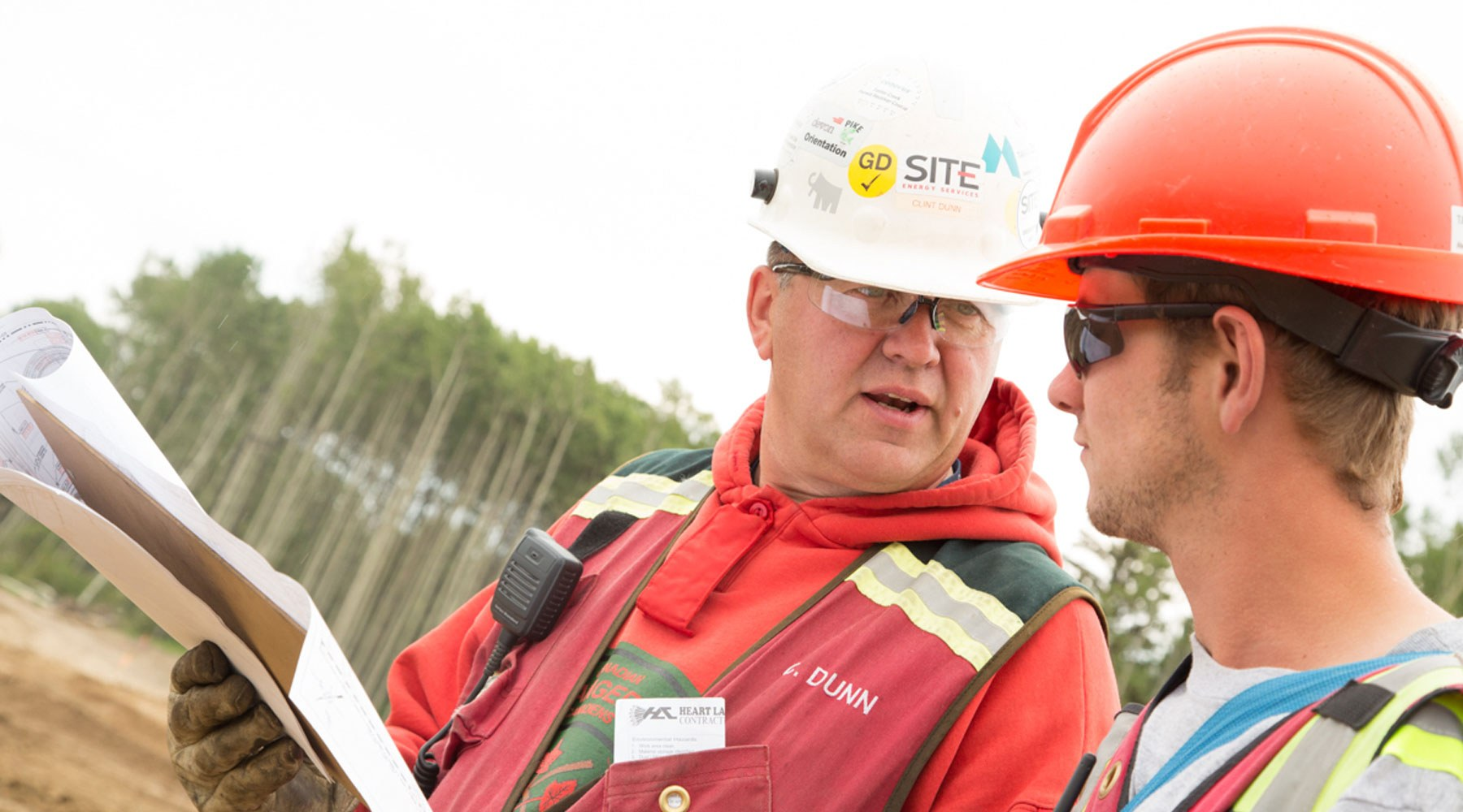 Image of two workers wearing PPE and hardhats, holding papers and conversing