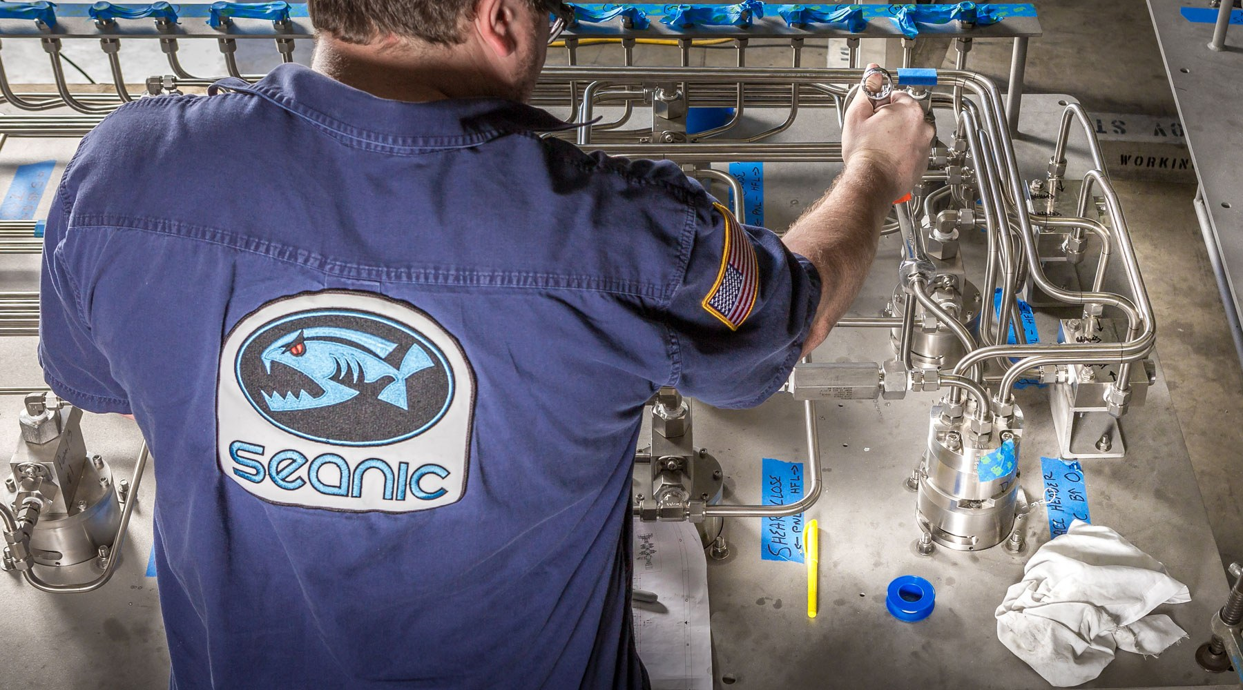 Man wearing Seanic-branded shirt carrying out work on equipment