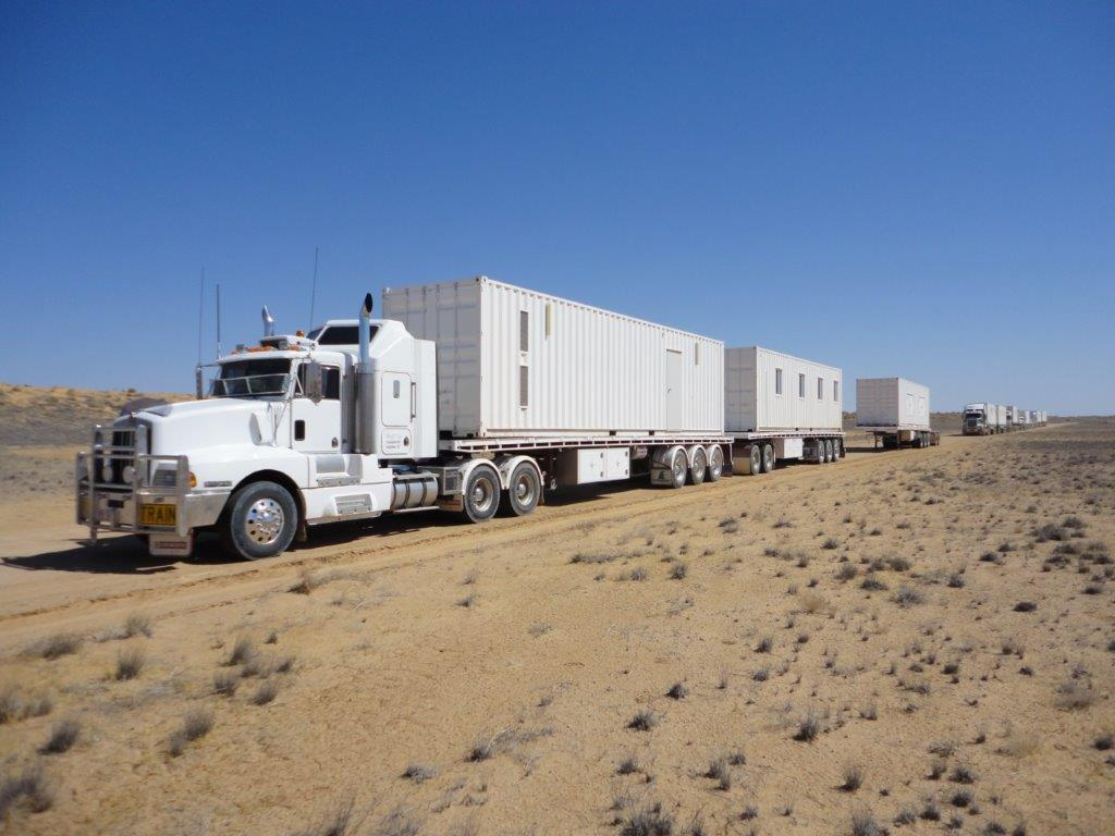 White haulage truck transporting trailers across a desert road