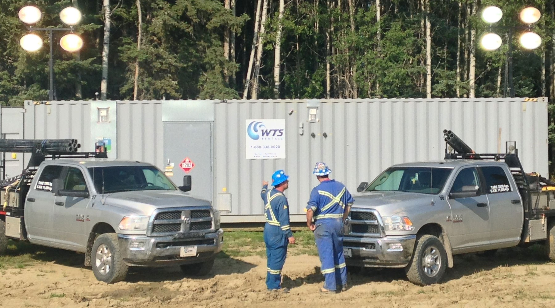 Two workers in blue PPE standing in front of a WTS-branded work trailer