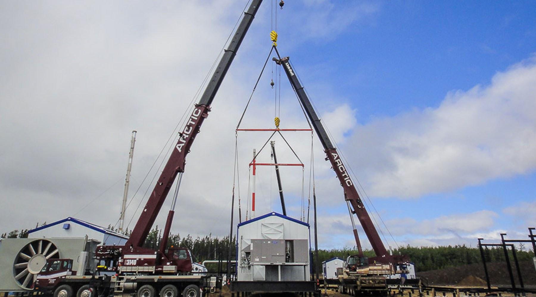Cranes hoisting an accommodation unit