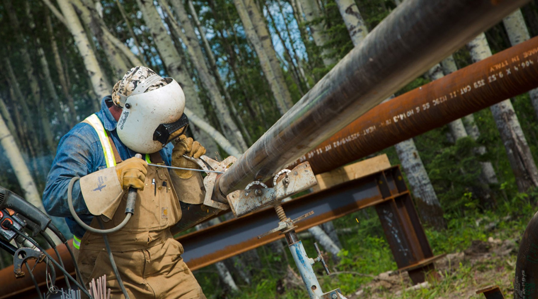 Worker performing maintenance on a pipe in a forest