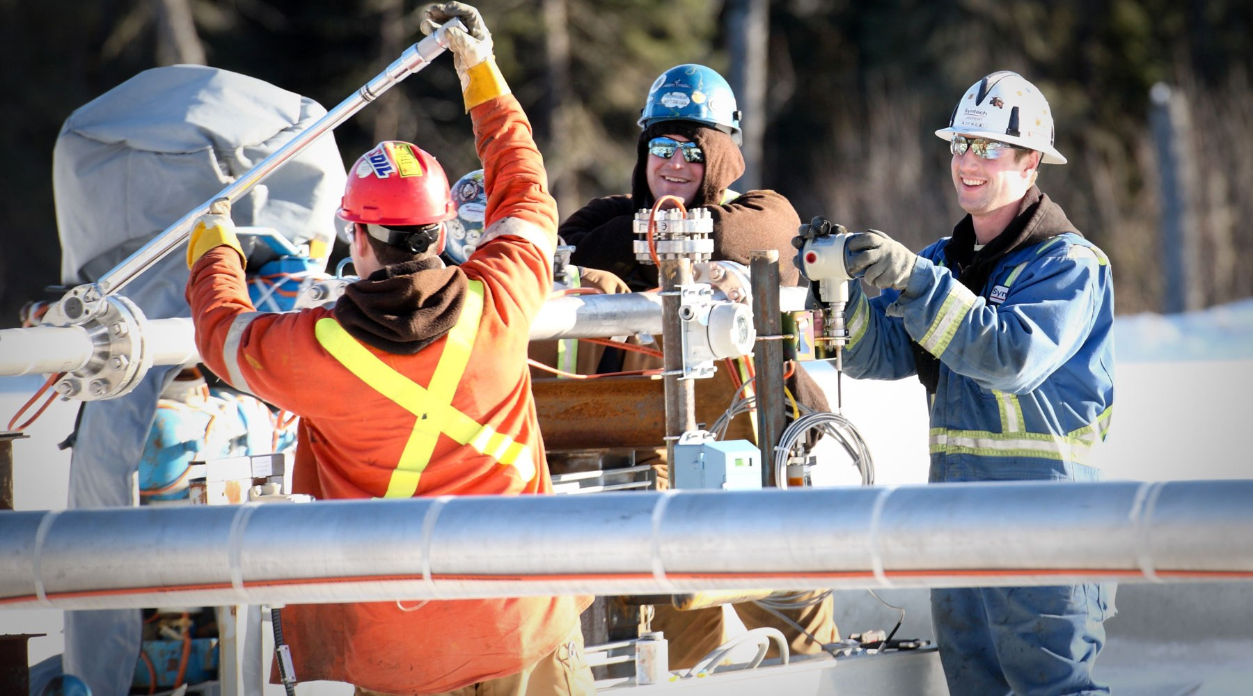 Three workers carrying out maintenance on pipeline equipment outdoors